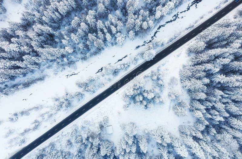 Opinión aérea sobre el camino y el bosque en invierno Paisaje natural del invierno del aire Bosque debajo de la nieve a invierno imagen de archivo libre de regalías