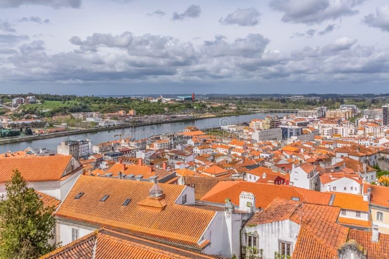 Opinión aérea sobre el río y los bancos de Mondego con la ciudad de Coímbra, cielo con las nubes como fondo, en Portugal foto de archivo