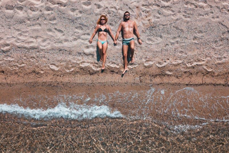 Opinión aérea sobre un par joven que miente en la playa foto de archivo libre de regalías