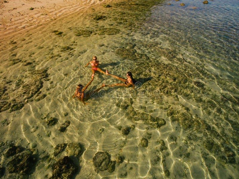 Opinión aérea tres mujeres jovenes que se sientan en el mar imagenes de archivo