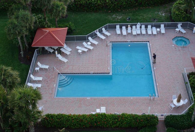 Opinión aérea un hombre que limpia una piscina del centro turístico imagen de archivo