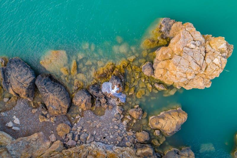 Opinión aérea una mujer joven que lleva un vestido blanco en las rocas Paisaje marino con una muchacha, playa, ondas hermosas, ro fotos de archivo