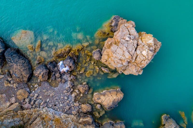 Opinión aérea una mujer joven que lleva un vestido blanco en las rocas Paisaje marino con una muchacha, playa, ondas hermosas, ro imágenes de archivo libres de regalías
