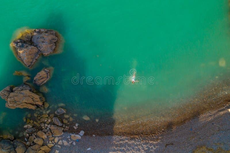 Opinión aérea una mujer joven que lleva un vestido blanco en las rocas Paisaje marino con una muchacha, playa, ondas hermosas, ro imagen de archivo libre de regalías