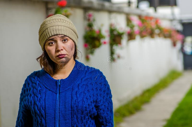 Opinión al aire libre la mujer sin hogar que pide en la calle en el tiempo frío del otoño que lleva una sudadera con capucha azul fotos de archivo libres de regalías