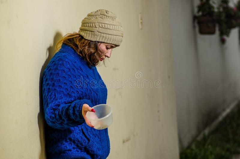 Opinión al aire libre la mujer sin hogar sola en la calle en el tiempo frío del otoño que sostiene un frasco plástico vacío en su imagen de archivo