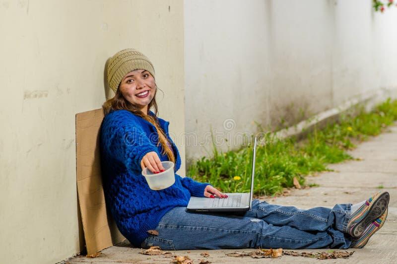 Opinión al aire libre la mujer sonriente sin hogar que pide en la calle en el tiempo frío del otoño que se sienta en el piso con  fotografía de archivo libre de regalías