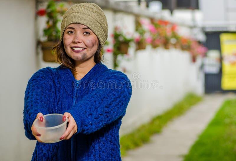 Opinión al aire libre la mujer sonriente sin hogar que pide en la calle en el tiempo frío del otoño sholding un frasco plástico v foto de archivo libre de regalías