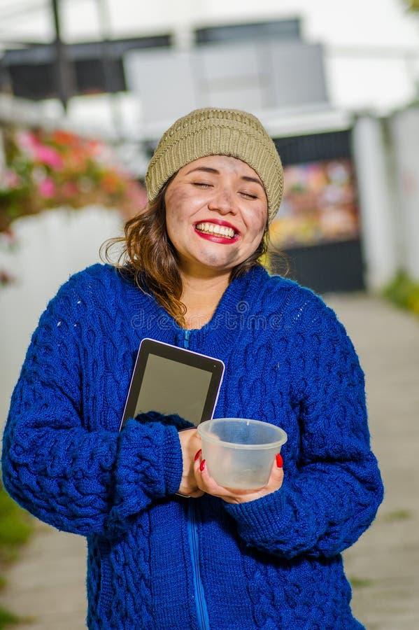 Opinión al aire libre la mujer triste sin hogar en la calle en el tiempo frío del otoño que sostiene un frasco plástico vacío en  imagenes de archivo