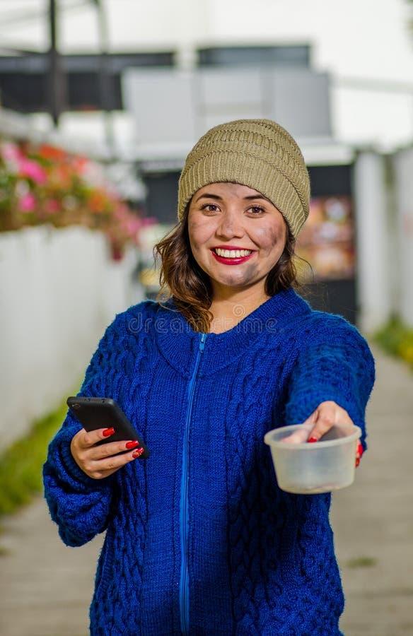 Opinión al aire libre la mujer triste sin hogar en la calle en el tiempo frío del otoño que sostiene un frasco plástico vacío en  imagen de archivo