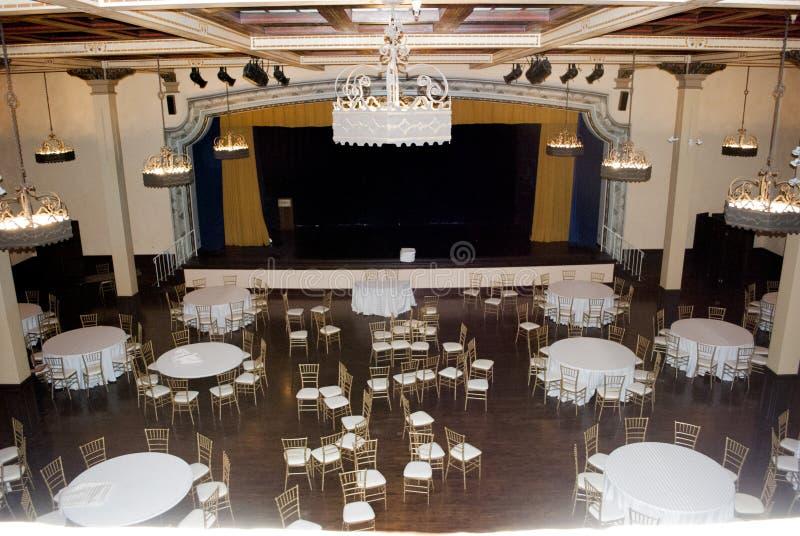 Opinión amplia sobre sitio de bola del banquete en estilo del vintage con la porción de tablas, de sillas y de escena del teatro imagen de archivo libre de regalías