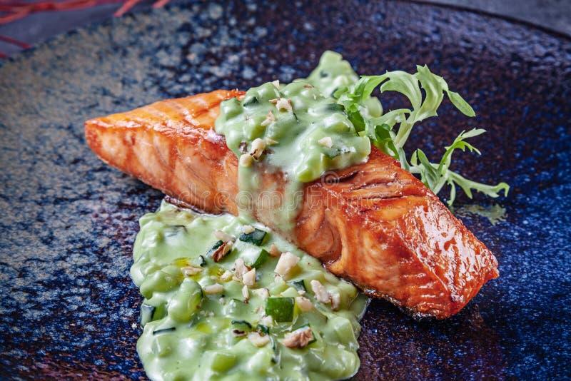 Opinión ascendente cercana sobre el filete de color salmón asado a la parrilla con la salsa verde en la placa oscura Pornograf?a  foto de archivo libre de regalías