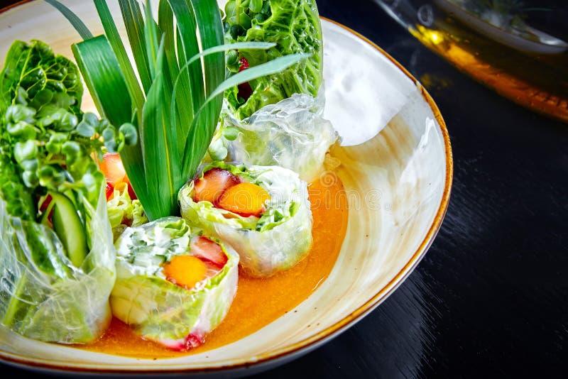 Opinión ascendente cercana sobre el rollo de primavera verde con la cebolla verde, el camarón y la crema en cuenco Foco selectivo fotografía de archivo libre de regalías