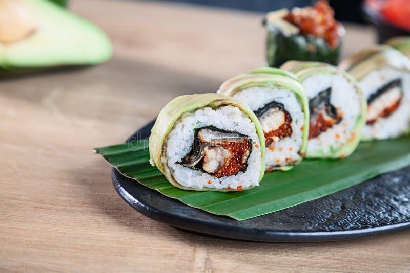 Opinión ascendente cercana sobre el sistema de rollo de sushi El rollo de California con los salmones, el aguacate y el caviar si foto de archivo