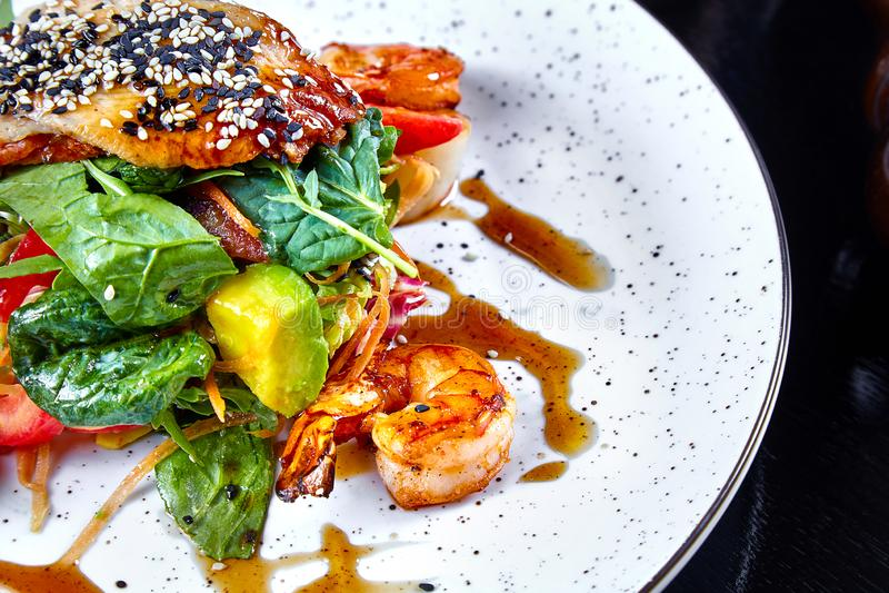 Opinión ascendente cercana sobre la ensalada caliente con el camarón, el aguacate, la espinaca y salmones en la placa del wjite C imagen de archivo libre de regalías
