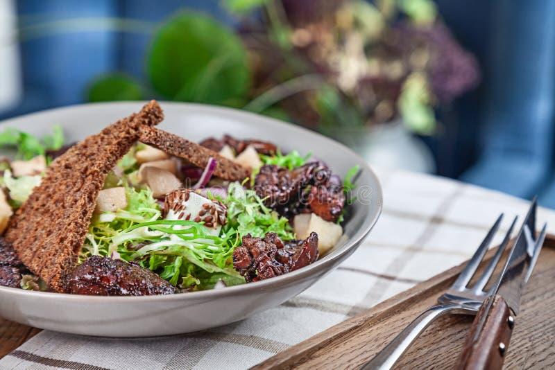 Opinión ascendente cercana sobre la ensalada sana fresca Ensalada con con lechuga, hígado de pollo, cuscurrones, las cebollas roj imagen de archivo