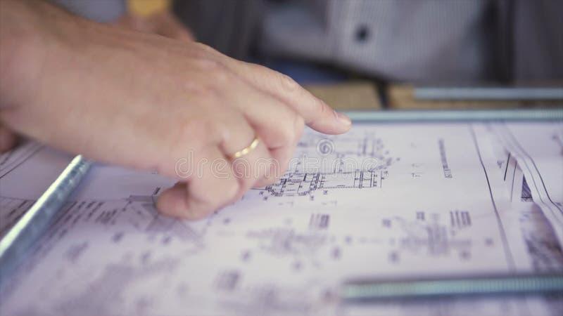 Opinión ascendente cercana sobre la mano del ingeniero que señala en los dibujos técnicos Manos de los hombres que indican alguno imagenes de archivo