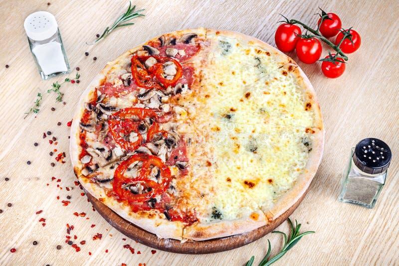 Opinión ascendente cercana sobre la pizza en el fondo de madera blanco con los ingridients Cocina italiana imagen de archivo