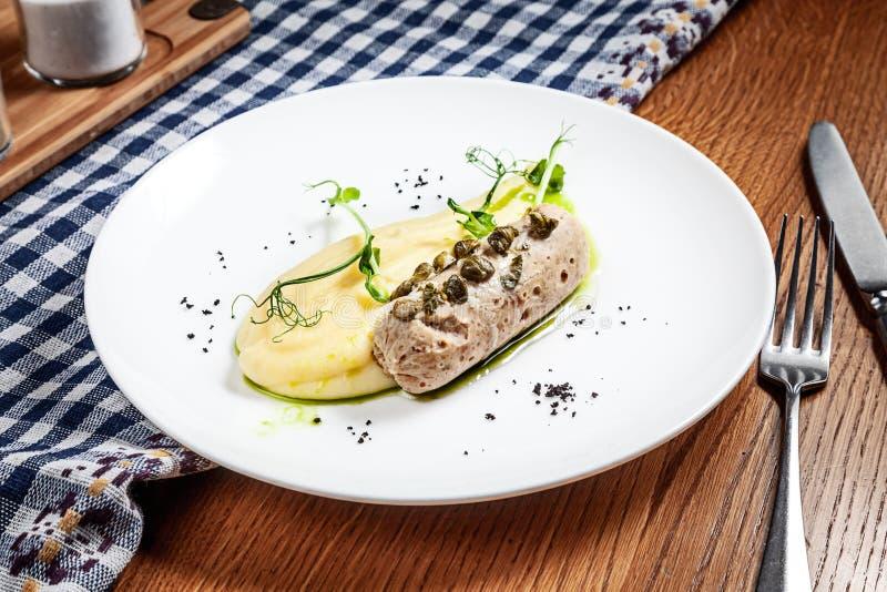 Opinión ascendente cercana sobre la salchicha de pescados con el puré de patata y microgreen en la placa blanca en fondo de mader imagenes de archivo