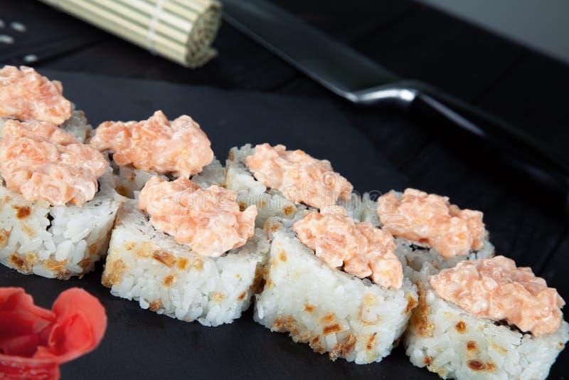 Opinión ascendente cercana sobre los rollos de sushi con con los pescados, el quingombó y el queso rojos de Philadelphia en un ta imágenes de archivo libres de regalías