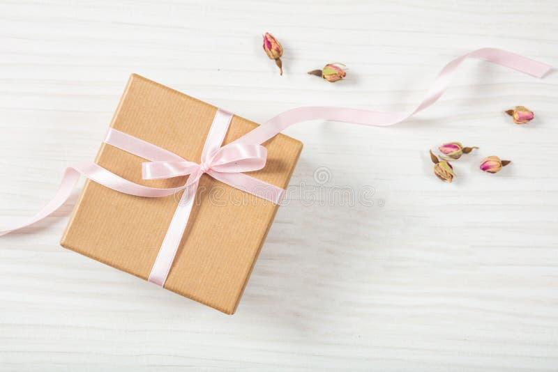 Opinión ascendente y superior del cierre de la caja de regalo beige del arte con la cinta sedosa rosada en un fondo de madera, es foto de archivo