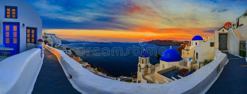 Opinión asombrosa de la puesta del sol del panorama con las casas blancas en el pueblo de Oia encendido foto de archivo libre de regalías