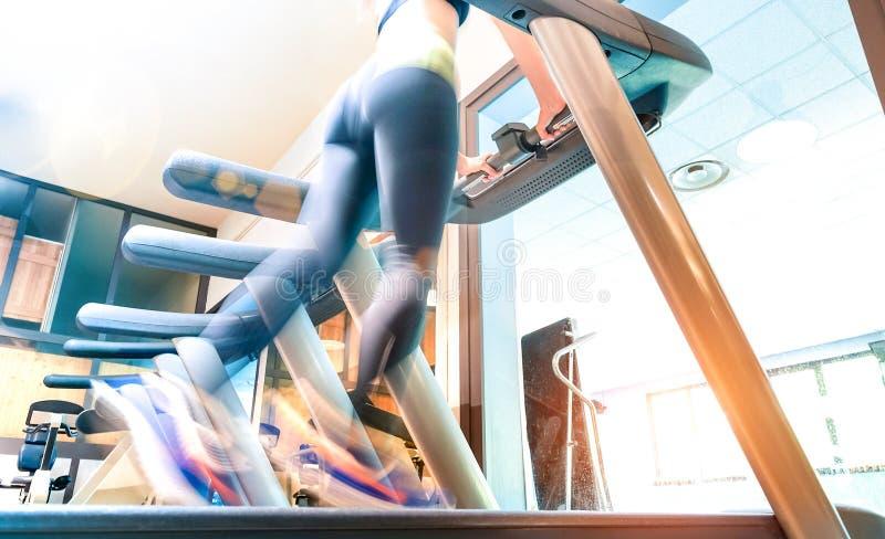 Opinión baja de la sección la deportista activa que corre en la rueda de ardilla en el estudio de la aptitud del gimnasio - conce imagenes de archivo