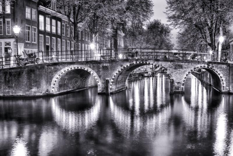 Opinión blanco y negro de la noche del paisaje urbano de Amterdam con uno de sus canales Con el puente iluminado y las casas hola imágenes de archivo libres de regalías