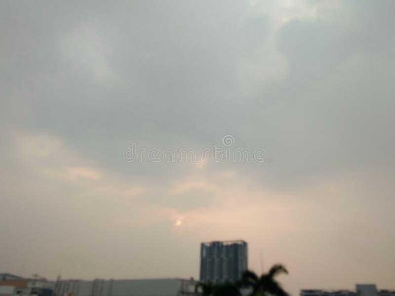 Opinión borrosa del cielo, sol que se mueve a la nube gris sobre el edificio fotografía de archivo libre de regalías