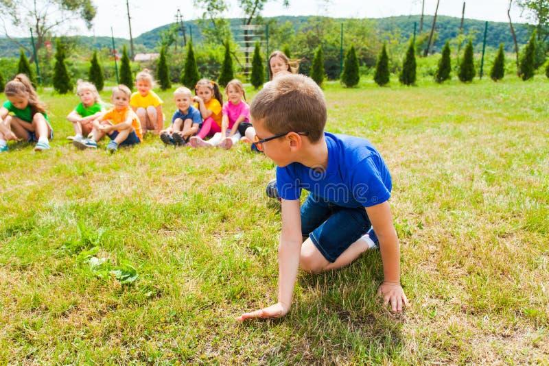 Opinión cercana el muchacho que se coloca en sus rodillas, grupo de niños detrás de él fotografía de archivo libre de regalías