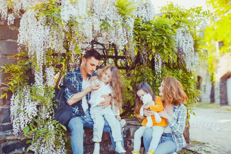 Opinión cercana la familia joven con dos niños que se sientan debajo de Glycinia fotografía de archivo