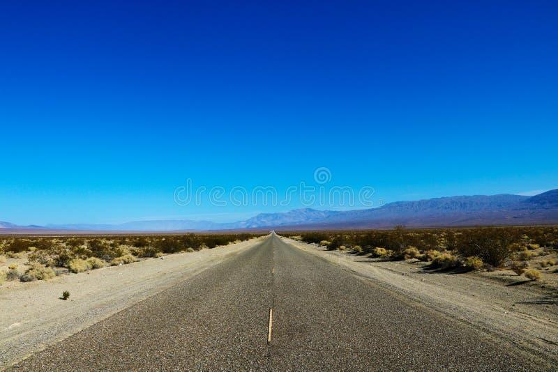 Opinión clásica del panorama de un camino recto sin fin que corre con el paisaje estéril del sudoeste americano con calor extremo imagenes de archivo