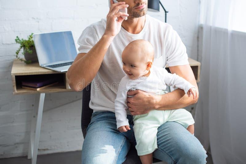 opinión cosechada el padre que se sienta en silla, hablando en smartphone y deteniendo a la hija sonriente del bebé fotos de archivo