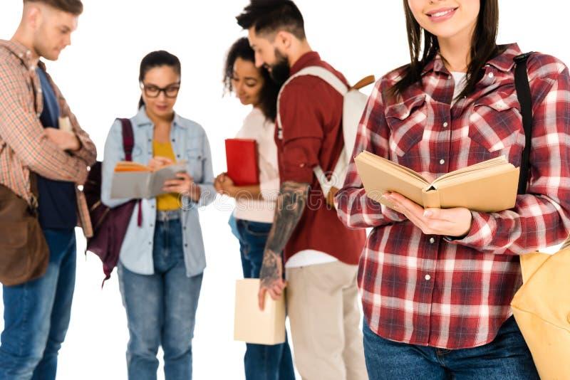 opinión cosechada la muchacha con el libro cerca del grupo multicultural de estudiantes jovenes aislados fotografía de archivo libre de regalías