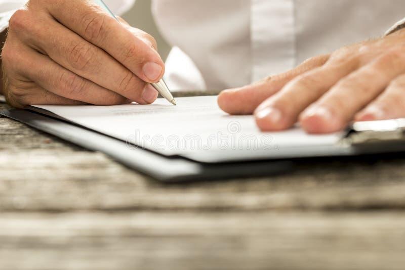 Opinión de ángulo bajo del contrato de firma o de la suscripción de la mano masculina para imágenes de archivo libres de regalías