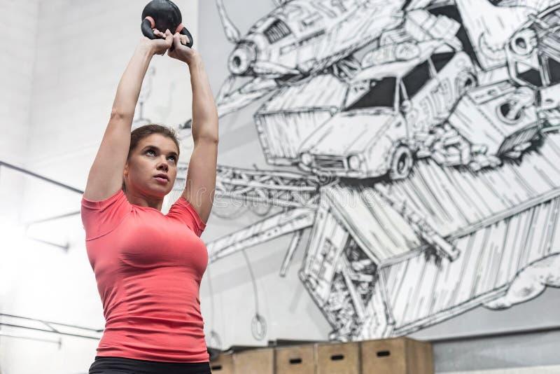 Opinión de ángulo bajo del kettlebell de elevación de la mujer dedicada en gimnasio del crossfit fotos de archivo