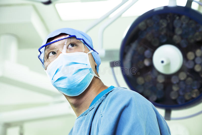 Opinión de ángulo bajo el cirujano que lleva una máscara quirúrgica y los vidrios en la sala de operaciones imágenes de archivo libres de regalías