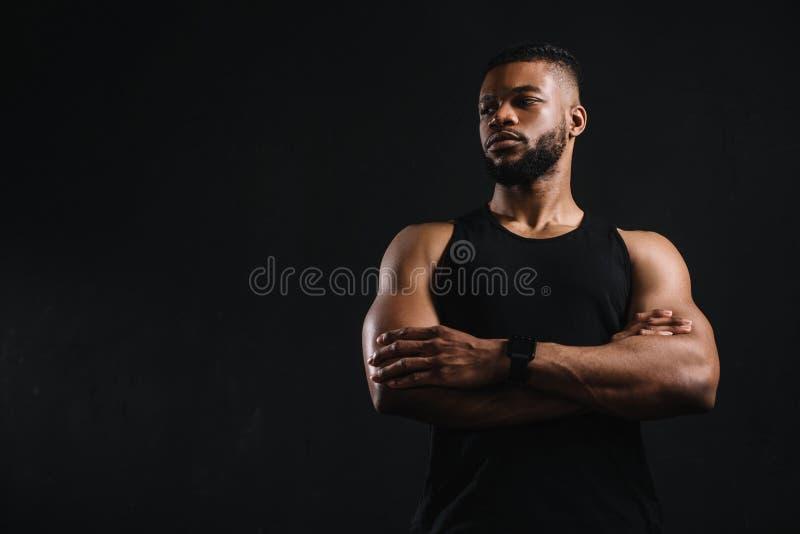 opinión de ángulo bajo el deportista afroamericano confiado que se coloca con los brazos cruzados y que mira lejos imagenes de archivo