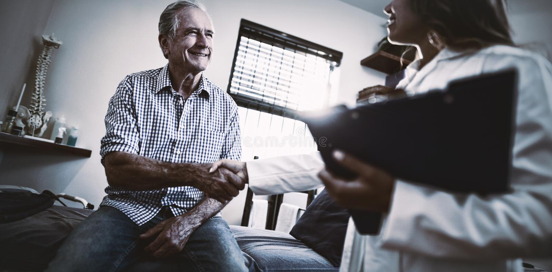 Opinión de ángulo bajo el terapeuta de sexo femenino y el paciente masculino mayor que sacuden las manos foto de archivo libre de regalías