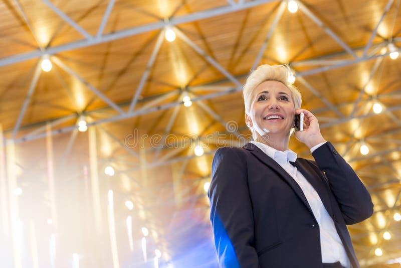 Opinión de ángulo bajo la empresaria rubia sonriente que habla en el teléfono elegante mientras que se opone al tejado iluminado foto de archivo