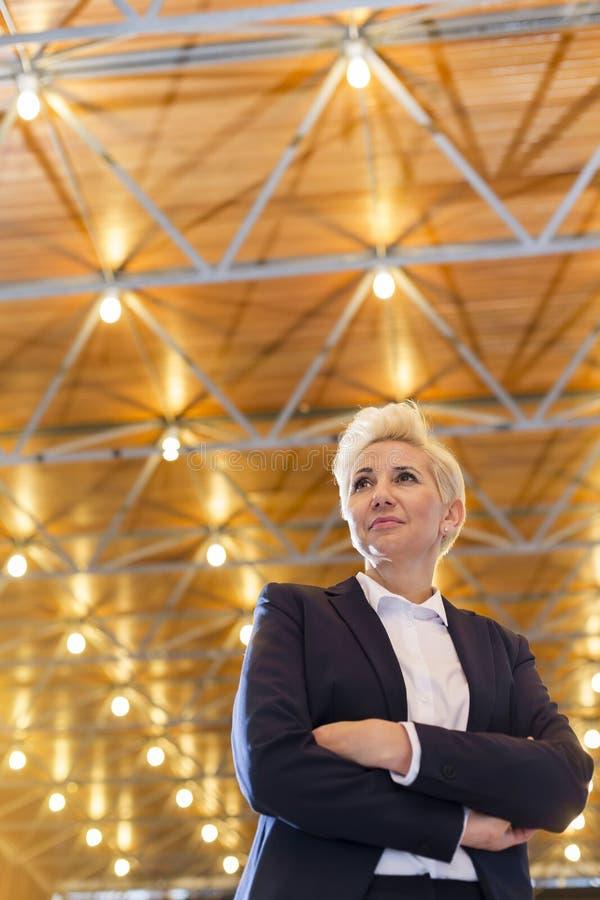 Opinión de ángulo bajo de la situación madura confiada de la empresaria con los brazos cruzados contra el tejado iluminado fotografía de archivo