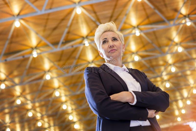 Opinión de ángulo bajo de la situación rubia confiada de la empresaria con los brazos cruzados contra el tejado iluminado foto de archivo
