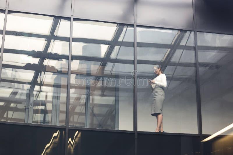 Opinión de ángulo bajo de la ventana que hace una pausa de la empresaria en la oficina fotos de archivo libres de regalías