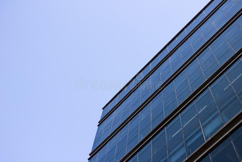 Opinión de ángulo bajo lateral de una pared azul de la ventana de cristal de un edificio de oficinas fotos de archivo