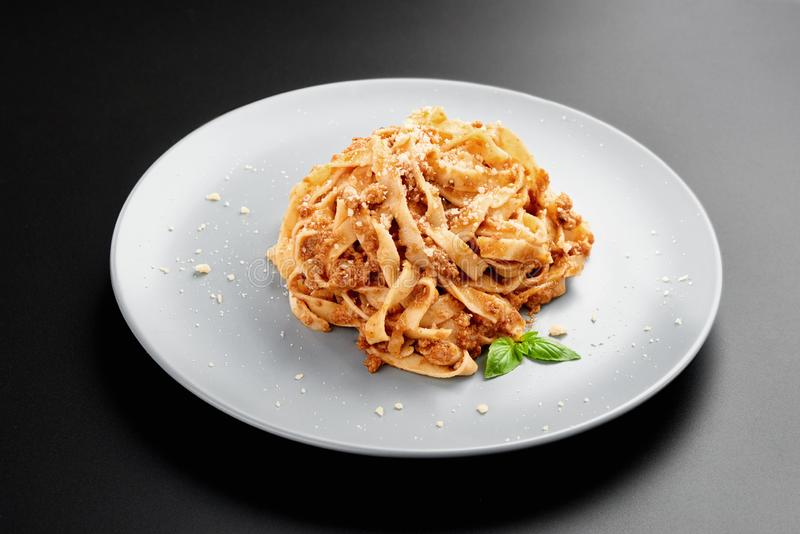 Opinión de ángulo bajo de los espaguetis boloñés con parmesano y albahaca púrpura, en un cuenco negro un fondo oscuro, fotografía de archivo libre de regalías