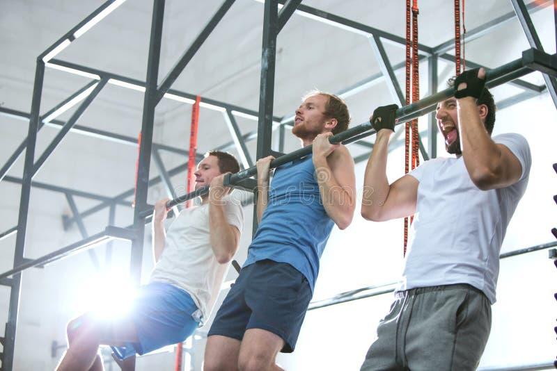 Opinión de ángulo bajo los hombres dedicados que hacen barbilla-UPS en gimnasio del crossfit imagen de archivo libre de regalías