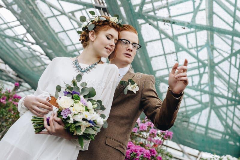 opinión de ángulo bajo de los pares jovenes hermosos de la boda del pelirrojo que se unen y que miran lejos imágenes de archivo libres de regalías