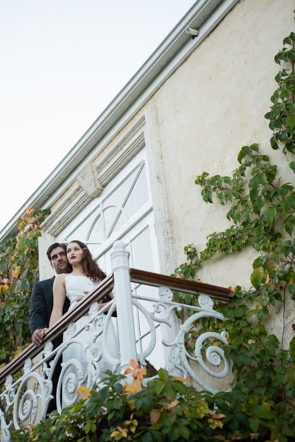 Opinión de ángulo bajo de los pares que abrazan mientras que se coloca en balcón foto de archivo