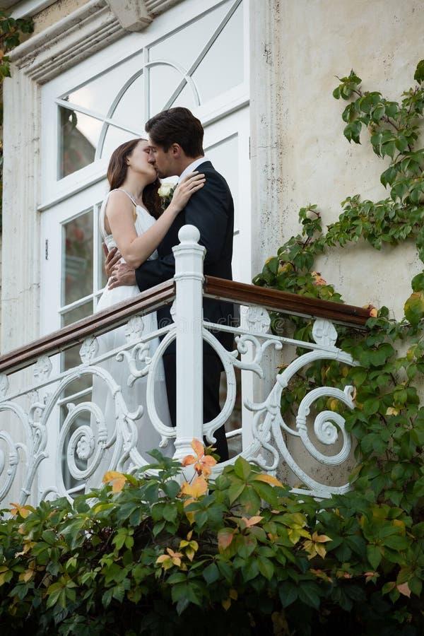 Opinión de ángulo bajo de los pares que se besan mientras que se coloca en balcón foto de archivo libre de regalías