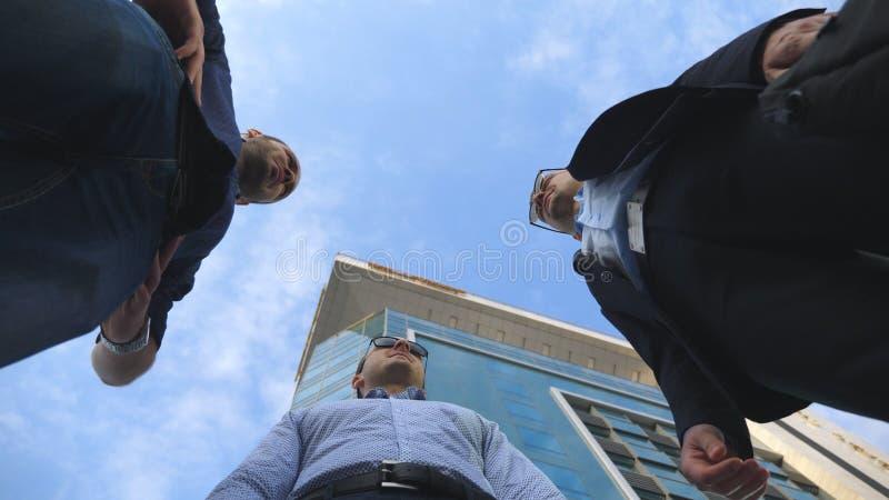 Opinión de ángulo bajo tres hombres de negocios que colocan la oficina cercana al aire libre y hablar Reunión de los hombres de n fotos de archivo libres de regalías